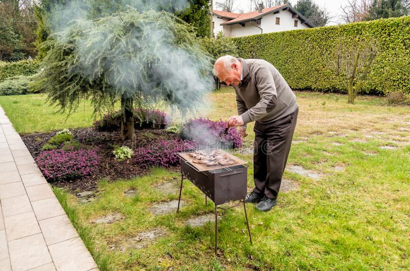 Senior Man grilling the meat on charcoal grill. Senior Man grilling the meat on charcoal grill outside in the garden royalty free stock image