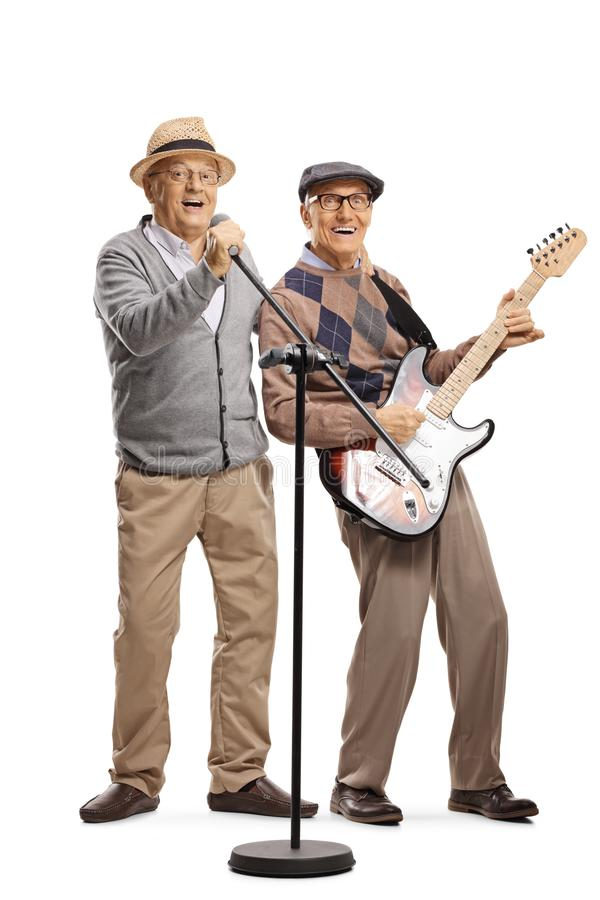 Senior man with a guitar and a senior man singing on a microphone royalty free stock image