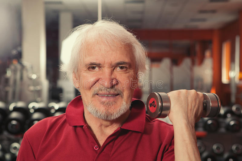 Senior man in gym working out with weights stock image