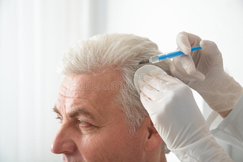 Senior man with hair loss problem receiving injection in salon stock image