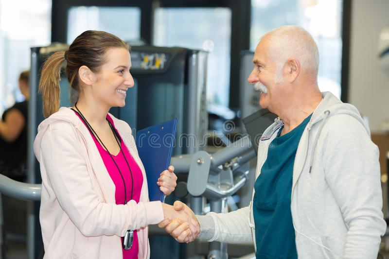 Senior man hand-shacking personal trainer in fitness studio stock photography