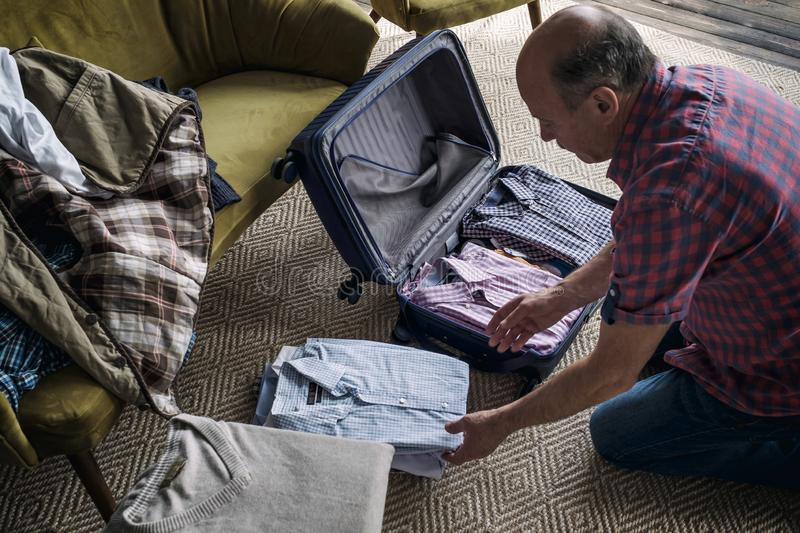 Senior man hands packing clothes in suitcase. Get ready for vacation stock photos