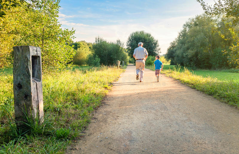 Senior man and happy child running outdoors. Back view of senior men with hat and happy child running on a nature path. Two different generations concept royalty free stock photos