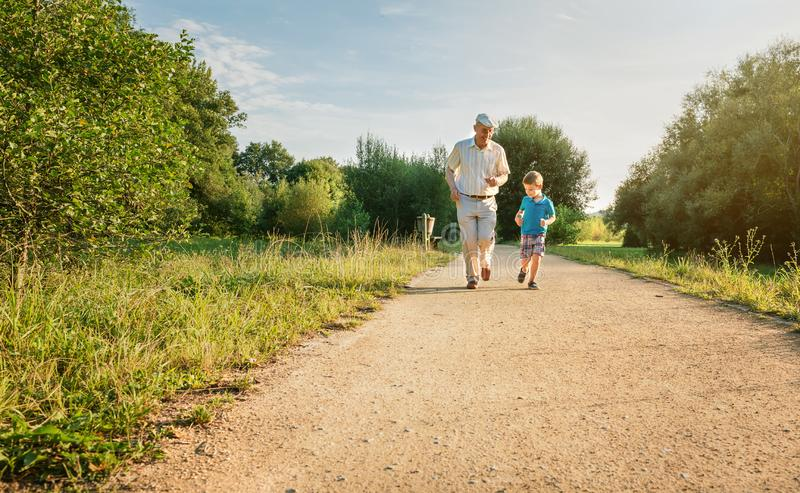 Senior man and happy child running outdoors. Front view of senior men with hat and happy child running on a nature path. Two different generations concept stock images