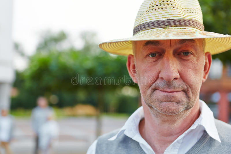 Senior man with hat looking neutral. Outside in a city stock photos