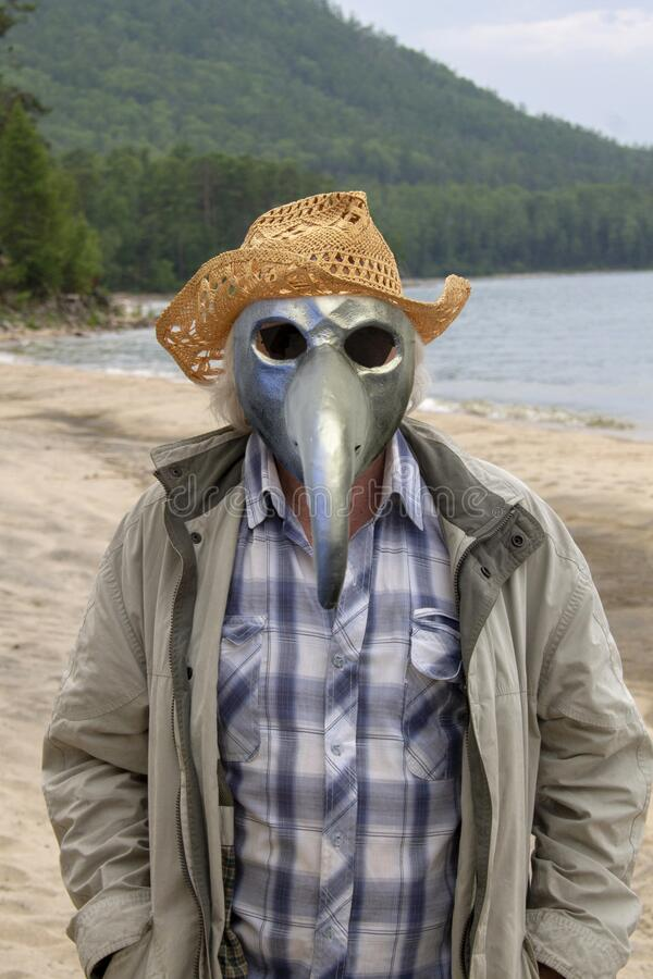 Senior man in a hat and a plague mask on the shore royalty free stock photos