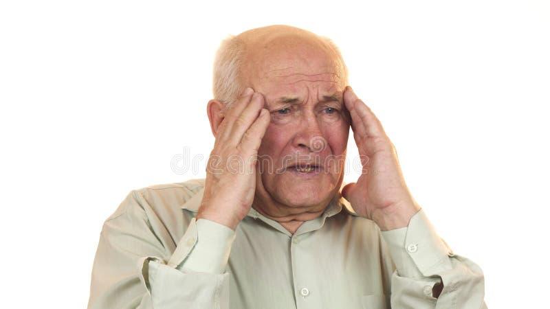 Senior man having a headache rubbing his temples royalty free stock image
