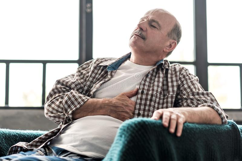 Senior man is having heart attack. Poor health at old age. Concept stock images