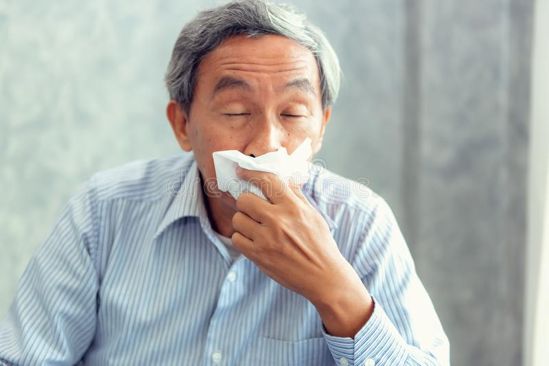 Senior man having sickness and sneezing into tissue, Healthcare. Senior man having sickness and sneezing into tissue., Healthcare concept stock photos