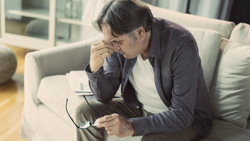Senior man with headache. At  home stock photo