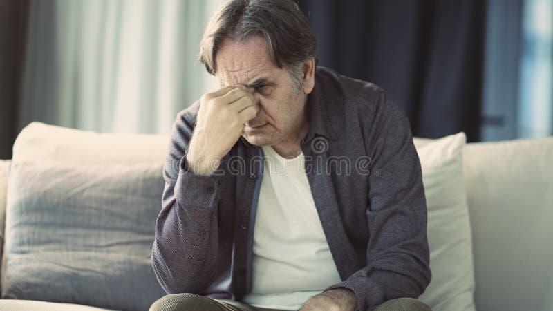 Senior man with headache at . home. Senior man with headache at home stock images