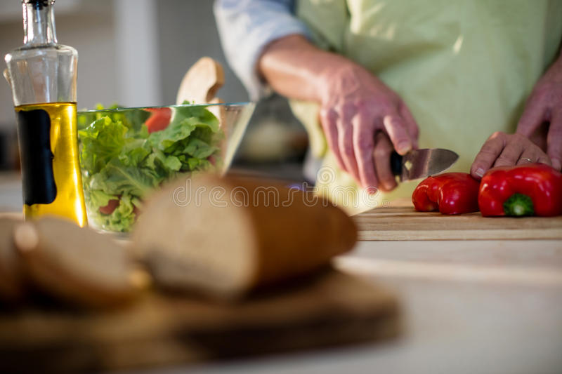 Senior man helping woman to cut vegetable in kitchen royalty free stock photography