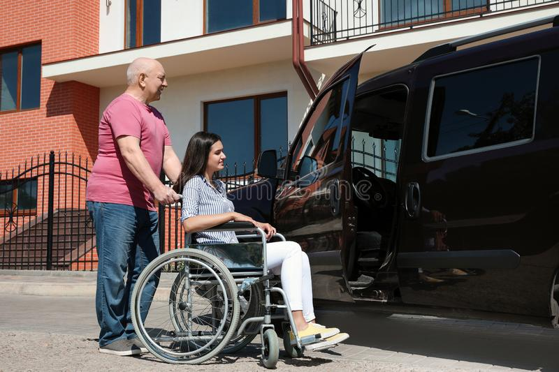 Senior man helping young woman in wheelchair to get into van. Senior men helping young women in wheelchair to get into van outdoors stock photos