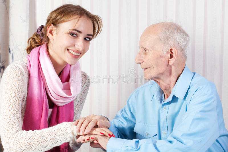 Senior man with her caregiver at home stock photography