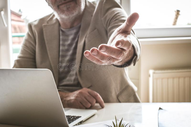 Senior man in his office giving helping hand. Close up. stock photos