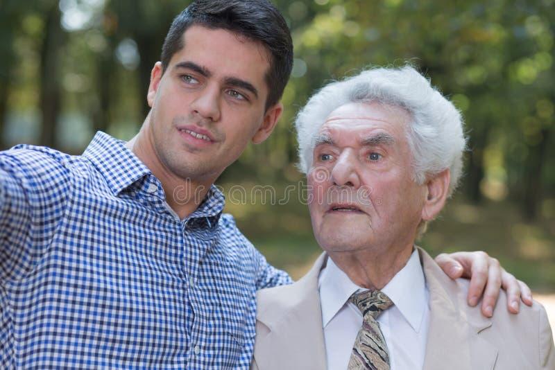 Senior man and his son. Photo of senior men and his son enjoying summer day royalty free stock photography