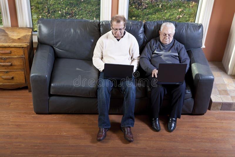 Senior man and his son using laptop computer royalty free stock photo