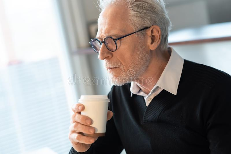 Senior man holding a coffee cup royalty free stock image