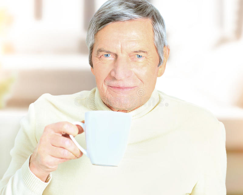 Senior man holding coffee mug, smiling at camera royalty free stock photo