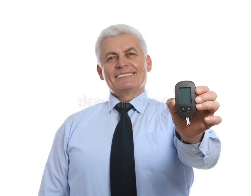 Senior man holding glucometer on white. Diabetes control stock images