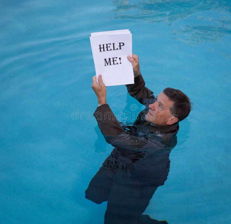 Senior man holding help me paperwork in water. Senior caucasian businessman in suit up to neck in deep blue water worried about drowning in paperwork and holding stock images