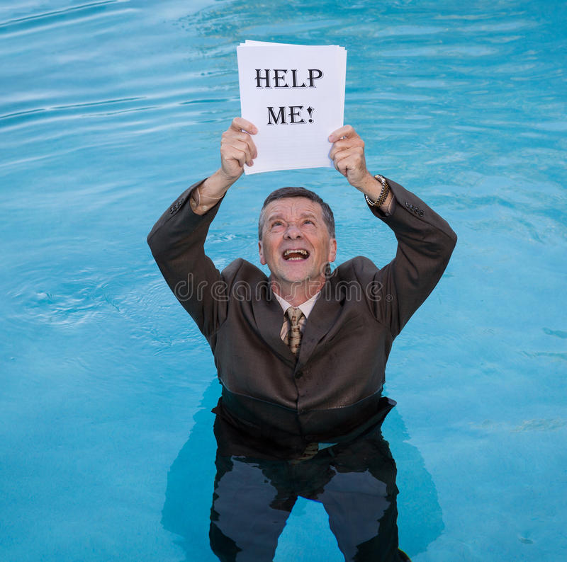 Senior man holding help me paperwork in water. Senior caucasian businessman in suit up to waist in deep blue water worried about drowning in paperwork and stock images