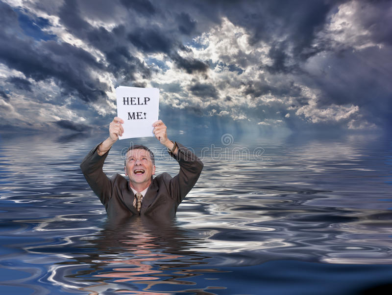 Senior man holding help me paperwork in water. Conceptual image of senior businessman in suit up to waist in deep water worried about drowning in paperwork and stock image