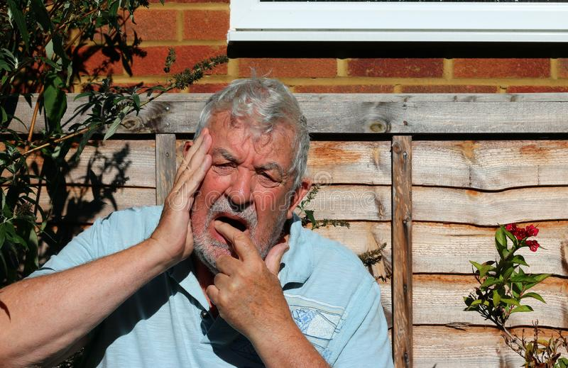 Tooth ache or pain. Senior man holding his face because of pain from tooth ache. Gums sore from teeth being bad royalty free stock photography
