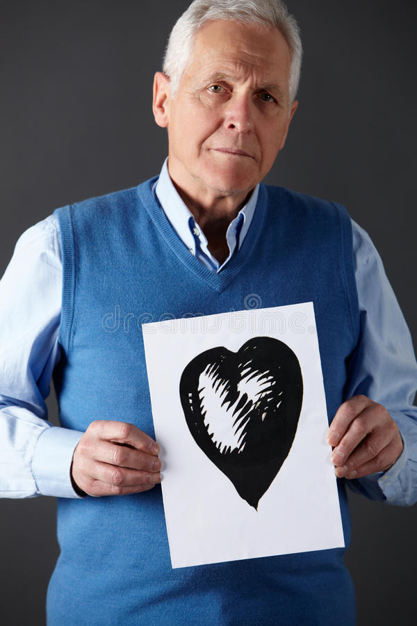 Senior man holding ink drawing of heart. Unhappy Senior man holding ink drawing of heart royalty free stock photography