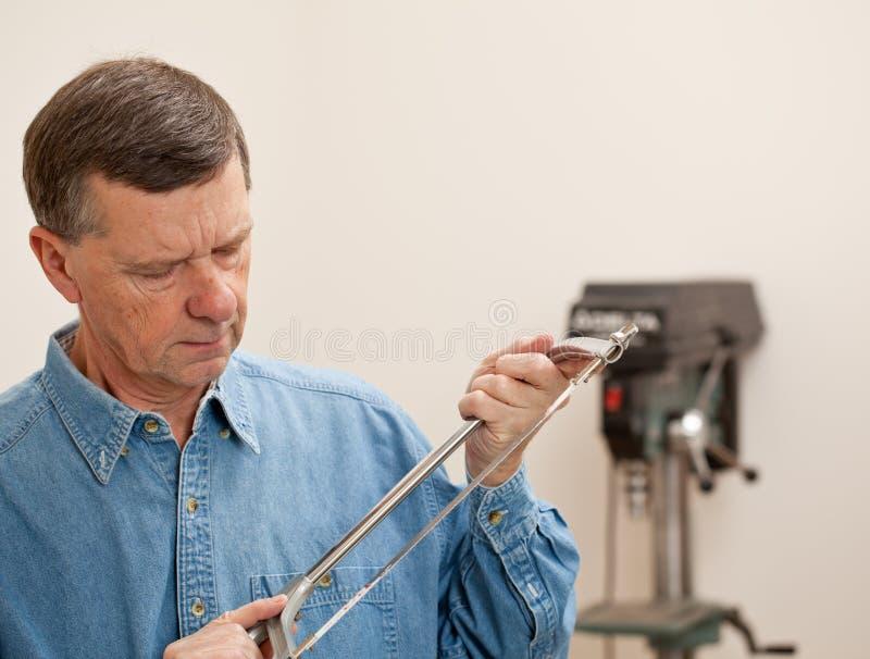 Senior Man Holding A Metal Saw Royalty Free Stock Photo