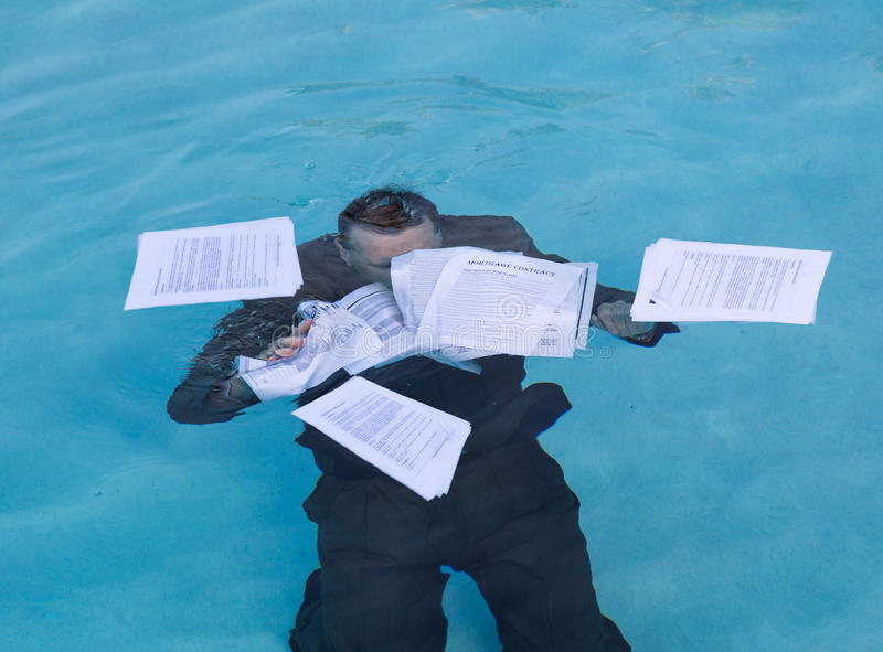 Senior man holding mortgage loan document in water. Senior caucasian businessman in suit sinking underwater in deep blue pool worried about being underwater with royalty free stock images