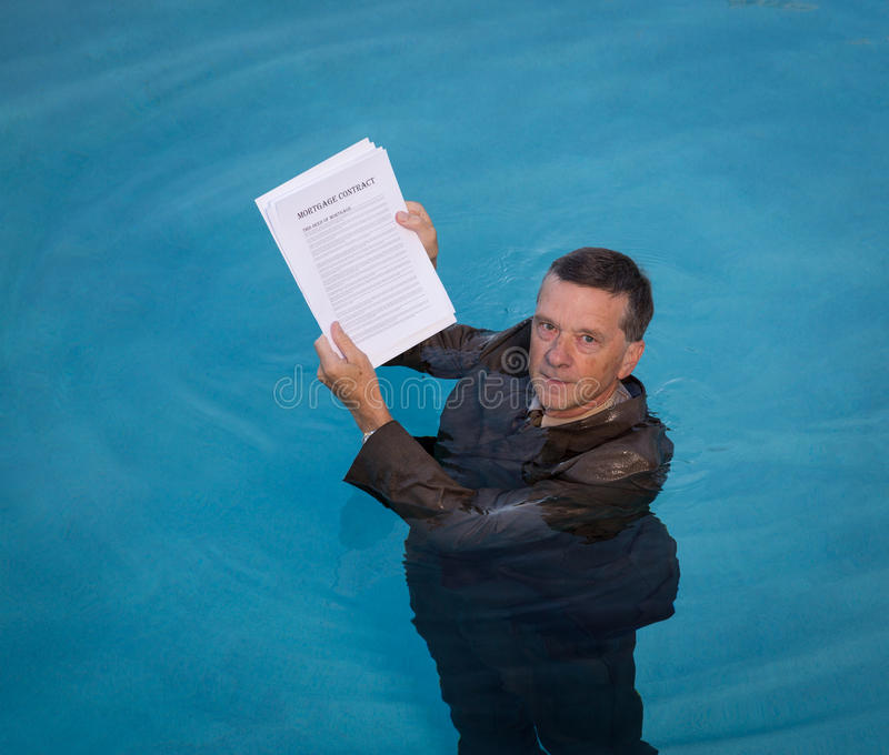 Senior man holding mortgage loan document in water. Senior caucasian businessman in suit up to neck in deep blue water worried about being underwater with royalty free stock photos