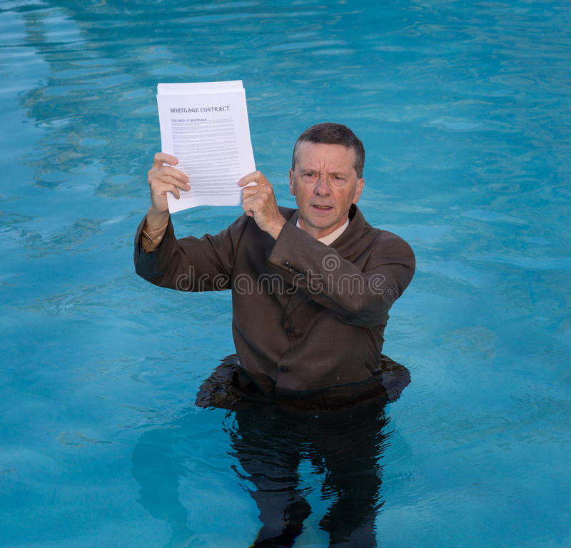 Senior man holding mortgage loan document in water. Senior caucasian businessman in suit up to waist in deep blue water worried about being underwater with stock photography