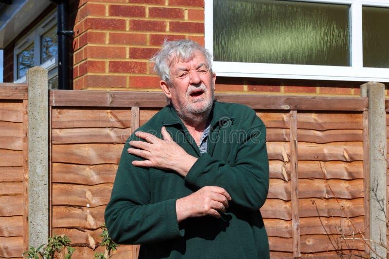 Senior man holding painful shoulder. A senior man in agony holding his painful shoulder. Either injured or arthritis stock photos
