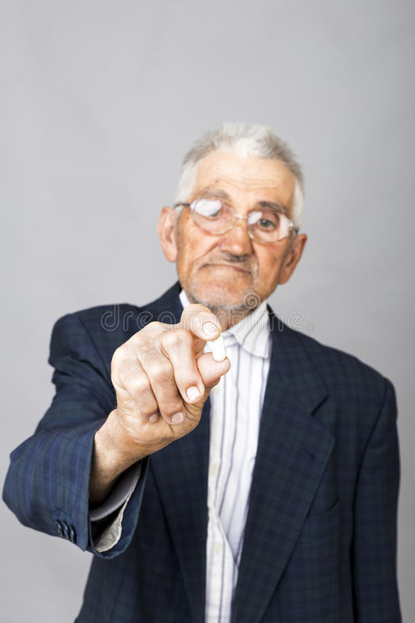 Senior man holding a pill ready to take some medicine stock images