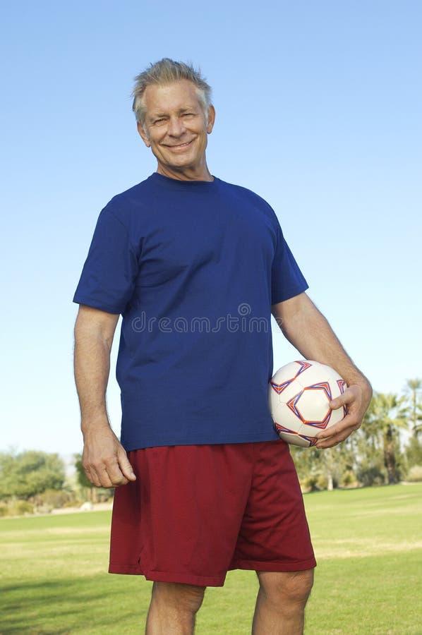 Senior Man Holding Soccer Ball At Park stock photo