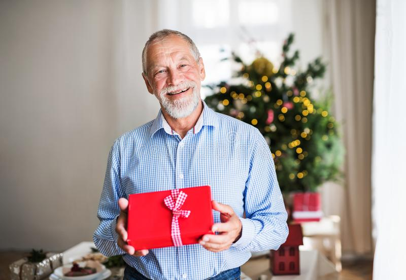 A senior man holding wrapped present at Christmas time. royalty free stock images