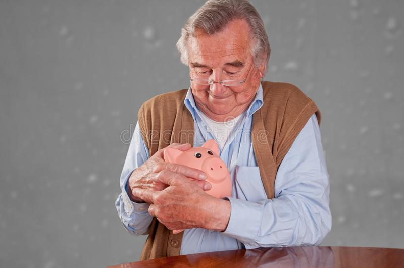 Senior man holds his piggy bank. Isolated on grey background stock photography