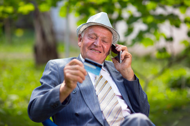 Senior man holds out a credit card cu laughs. Using the phone stock photography