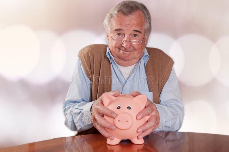 Senior man holds piggy bank to save money. Worried senior man hold piggy bank with money in his hands stock photography