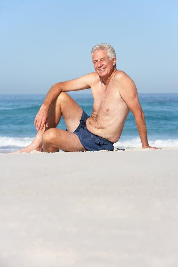 Senior Man On Holiday Sitting On Beach Stock Photo