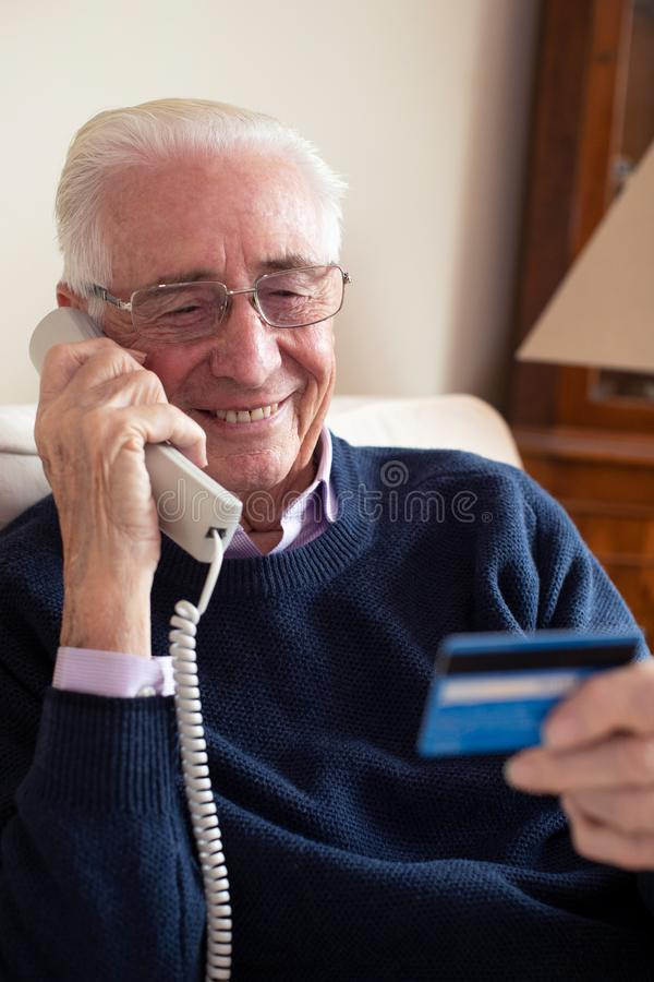 Senior Man At Home Giving Credit Card Details On The Phone royalty free stock photo