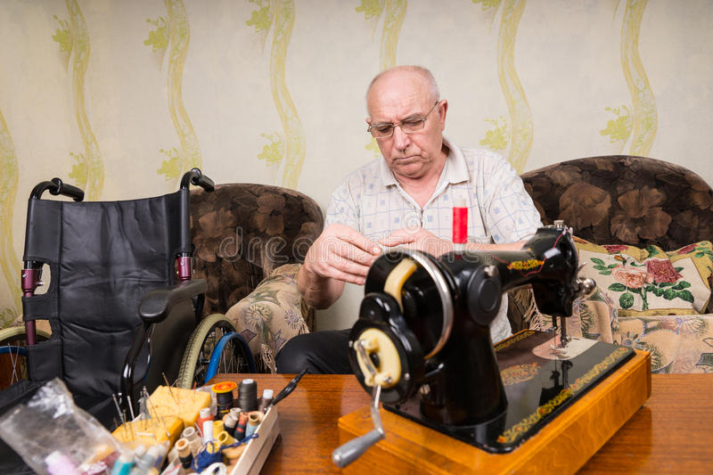 Senior Man at Home with Vintage Sewing Machine stock photography