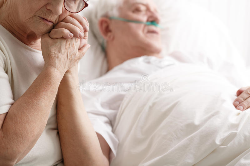 Senior man in hospital bed and his wife holding his hand. Dying senior men in hospital bed and his sad wife holding his hand stock photo