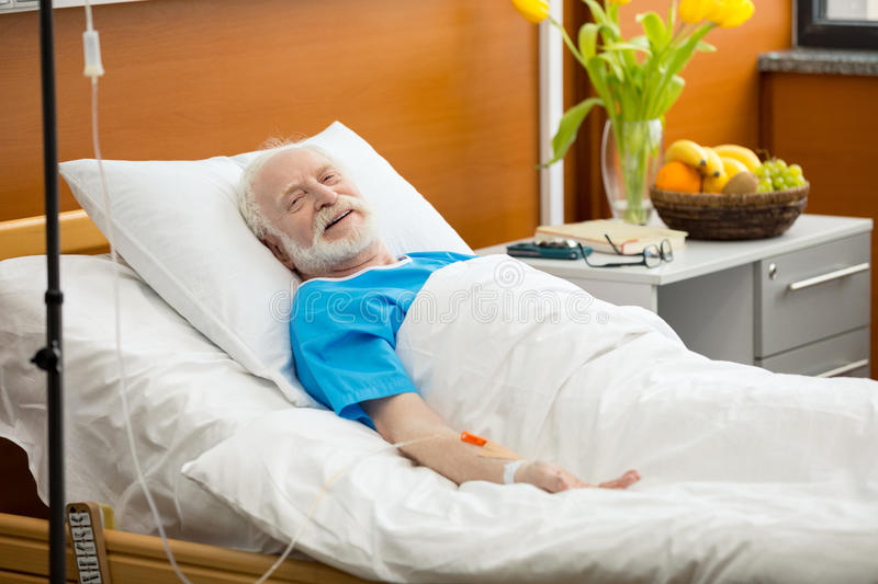 Senior man in hospital bed stock image