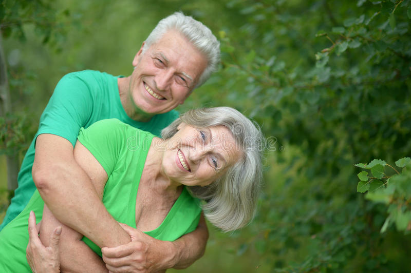 Senior man hugging senior woman in forest royalty free stock images