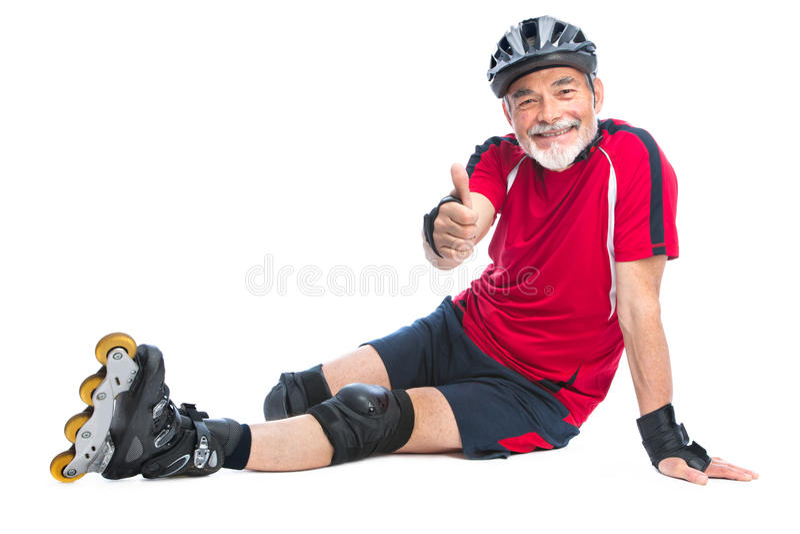 Senior man inline skating. Senior man goes inline skating and shows thumbs up royalty free stock photography