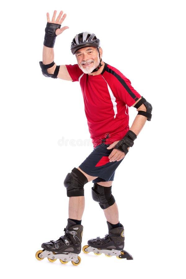 Senior man inline skating. Senior man goes inline skating royalty free stock photography