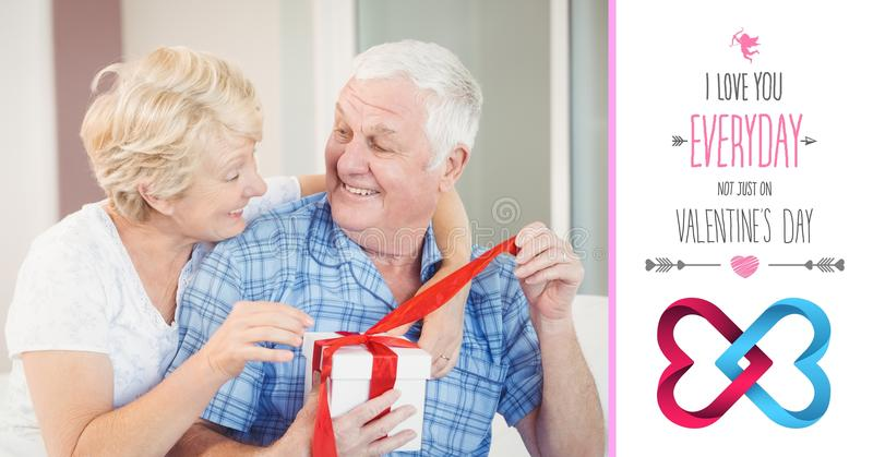 Senior man interacting with woman while opening gift box. Composite of senior man interacting with woman while opening gift box stock image