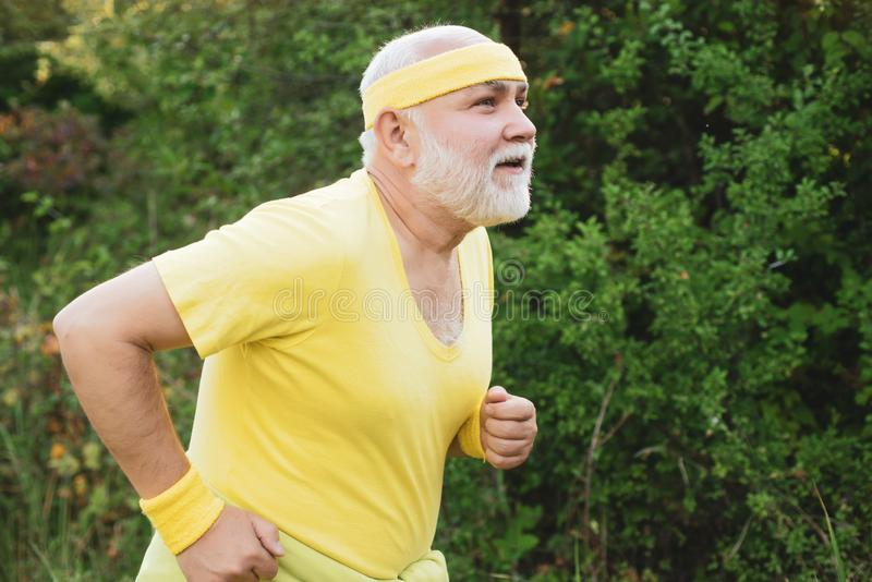Senior man jogging in park. Like sports. Funny sporty old sportsman finished his work out. Old sport man running outside stock photos
